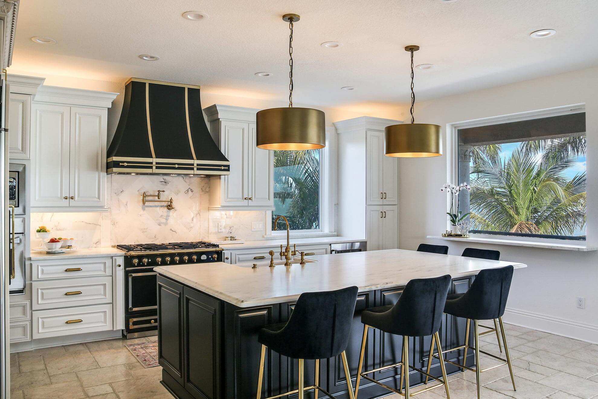 Traditional kitchen with chandelier and large custom range hood made from stainless steel with gold trim and rivets.