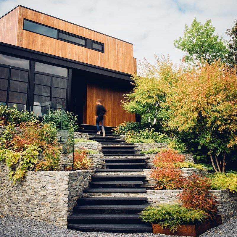 Une homme monte les marches d'une maison architecturale