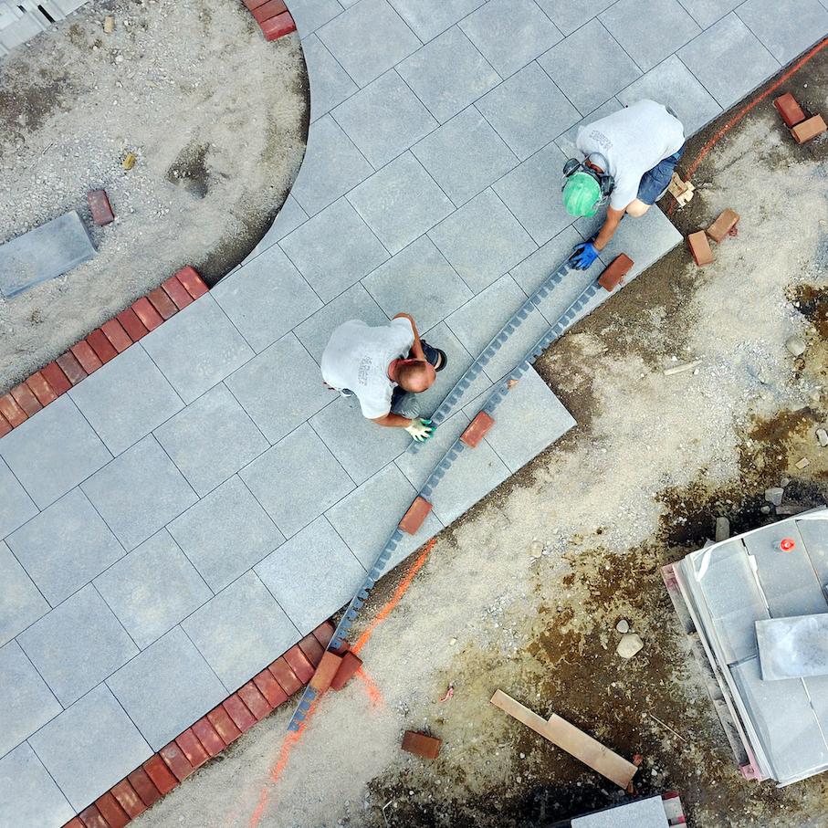 Deux hommes installent des briques et des dalles de béton pour faire un trottoir