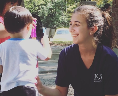 Decorative image: a volunteer talking to a young kid