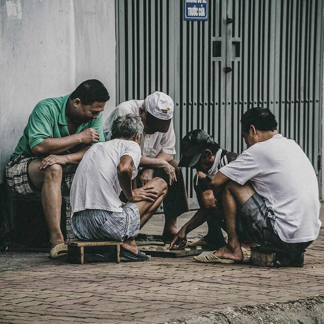 Photo of group of men sitting on sidewalk