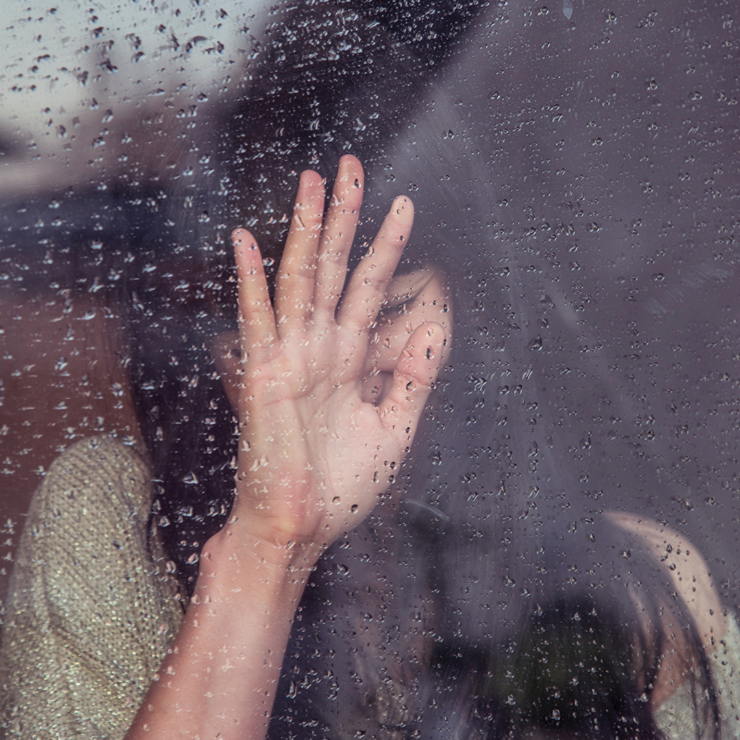 Photo of woman behind window with rain drops on it. Her hand is on the window and she seems sad.