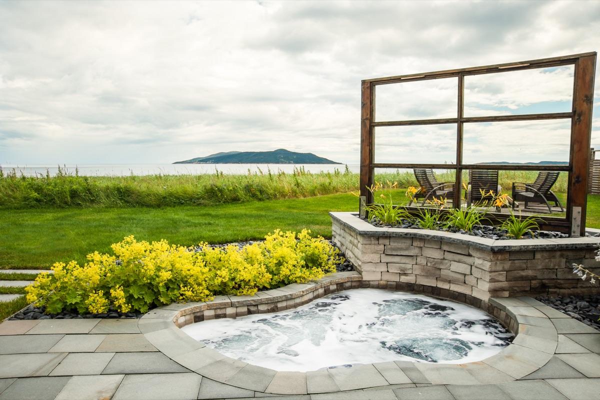 Aménagement d'un spa intégré avec muret et patio de pierre naturelle
