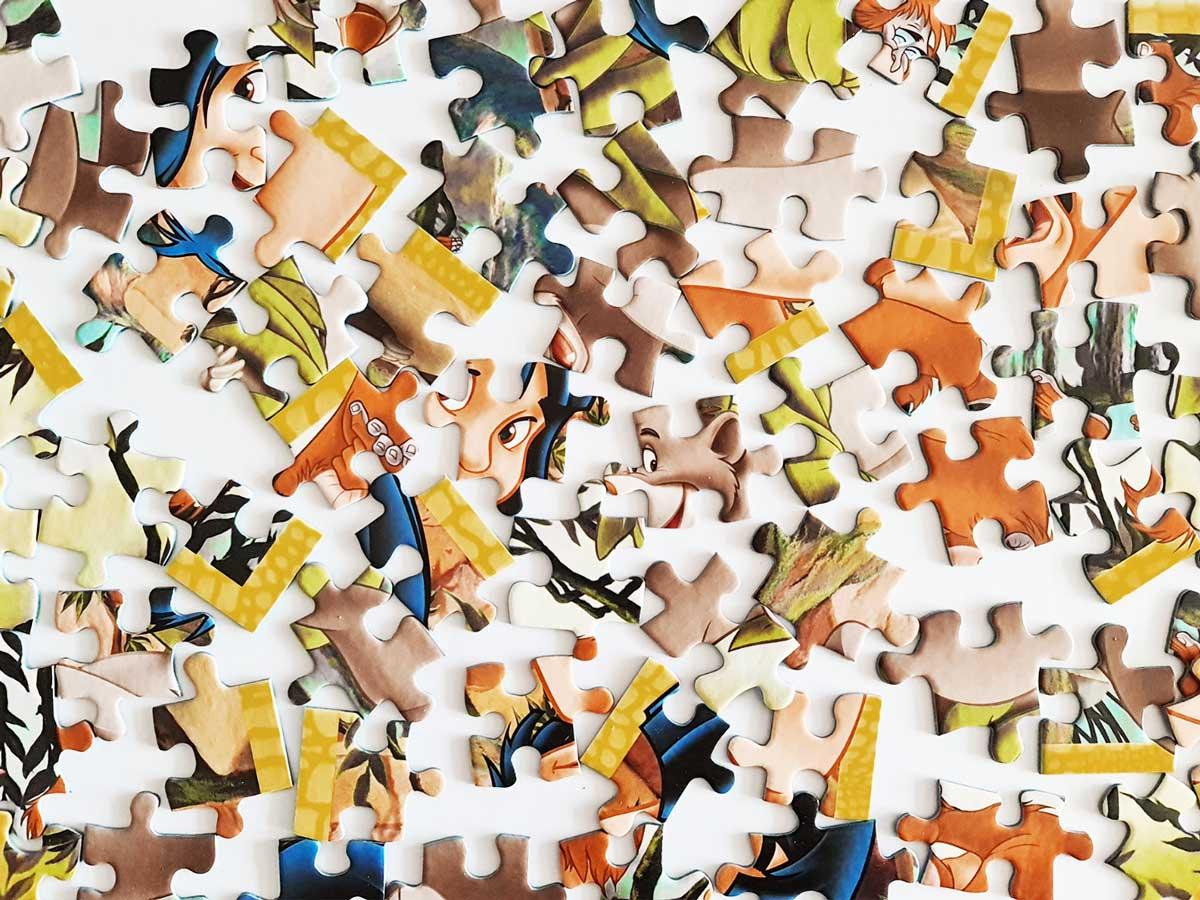Verschiedenfarbige Puzzleteile verteilt auf einer weissen Unterlage.