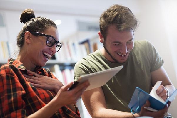 to studenter som leser i bøker og smiler