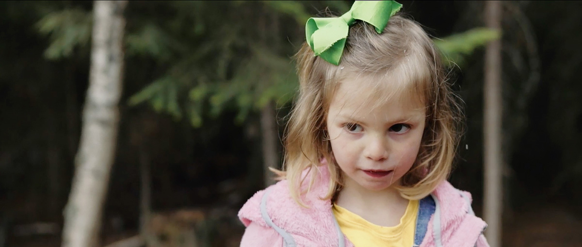 a young girl with a pink jacket and a green bow in her hair.