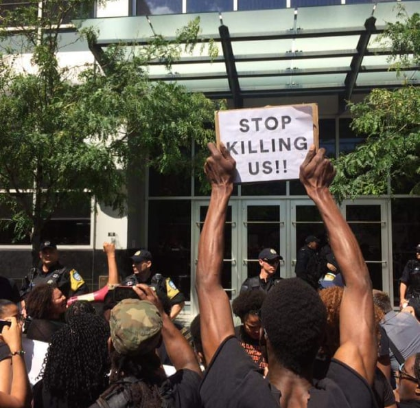 "Person holding sign that reads ""stop killing us"""