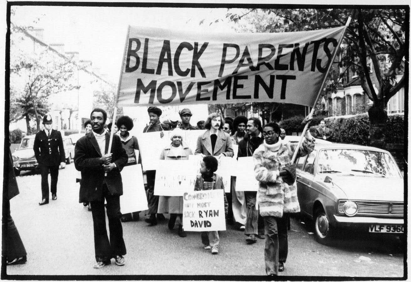 Street march moving towards camera with Black Parents Movement banner held aloft. John La Rose can be seen in the middle of the group, engaged in conversation. The march is taking place on a residential street to reflect the local nature of the campaign and to attract support from the community.