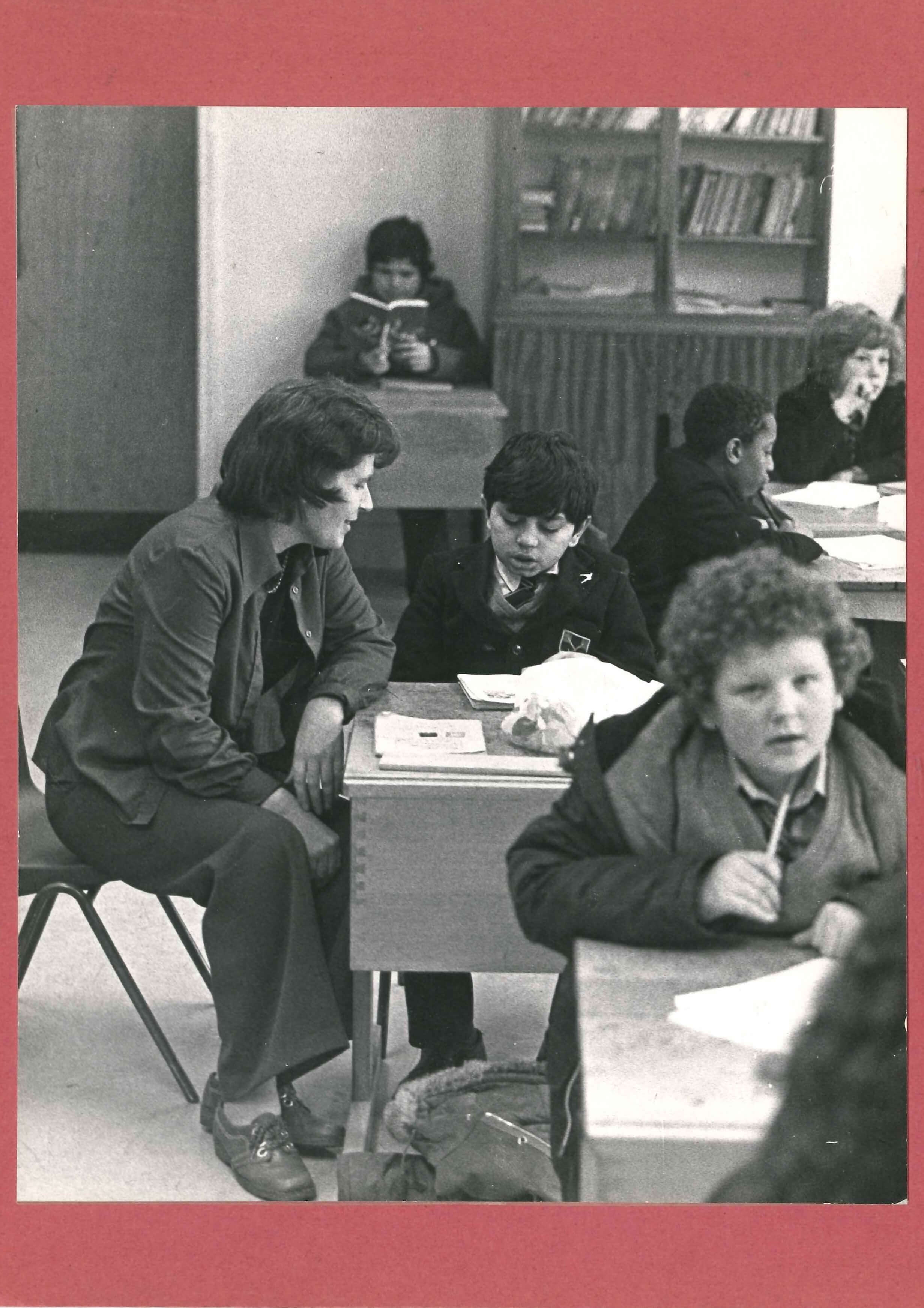 Joan Goody is shown sitting in a classroom at the desk of a primary school child, helping him to read a book. Other children are shown reading and writing.