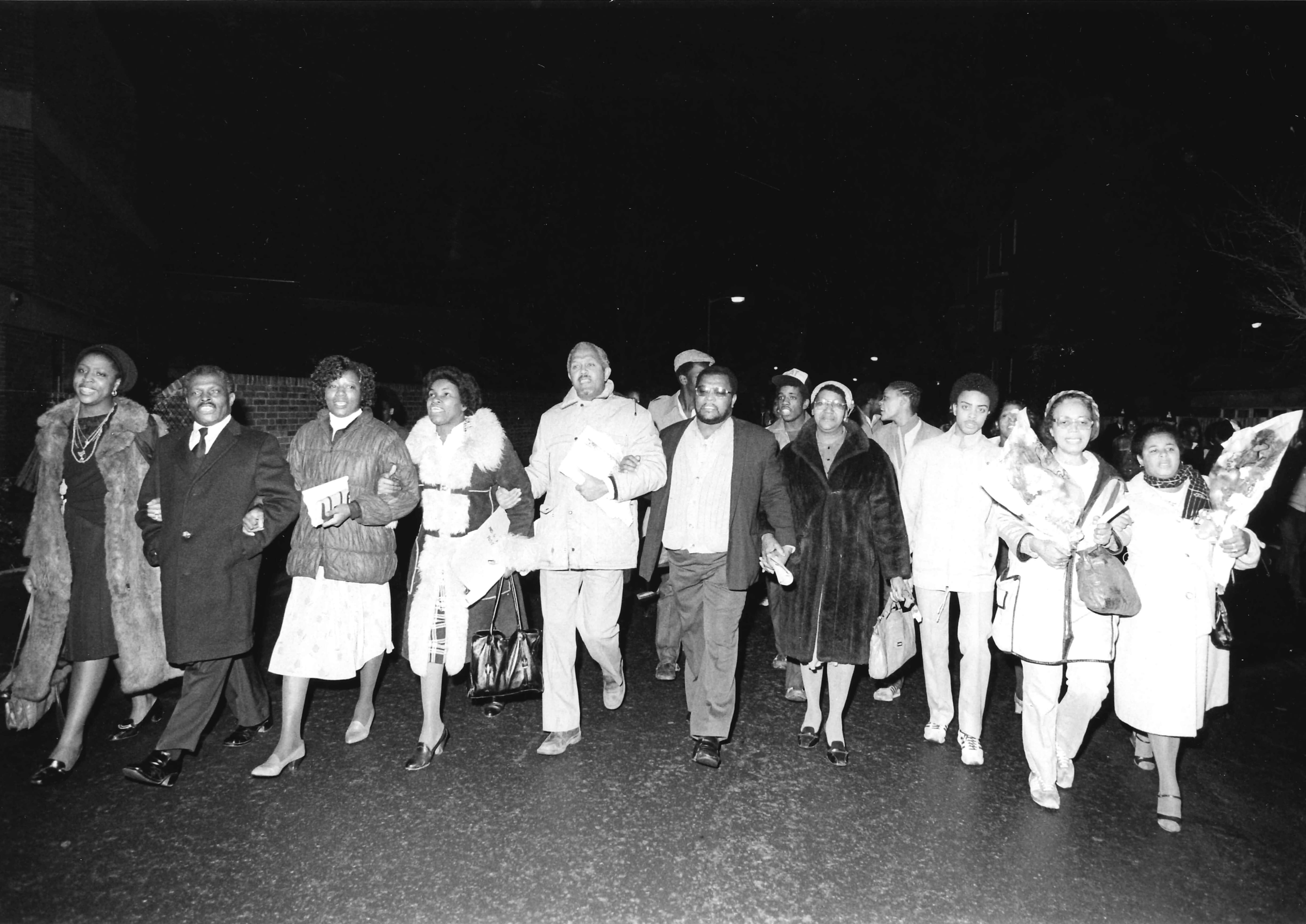 Photo taken at night, with John La Rose (centre) and the families of victims walking together, with their arms linked. Shown illuminated by light, against the dark sky.