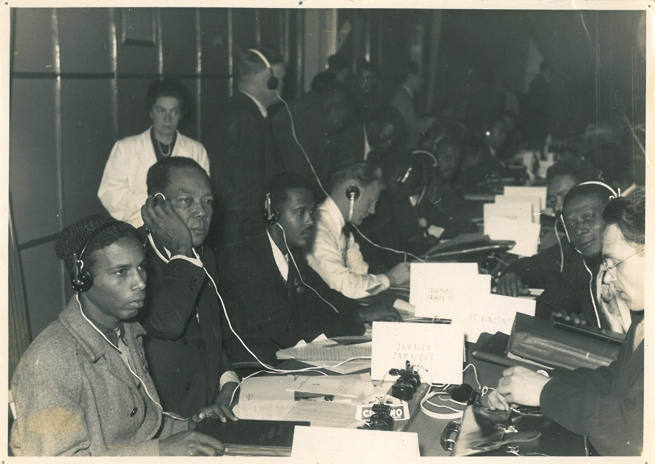 Delegates seated shoulder to shoulder down a long, narrow table in a poorly lit room. They are listening to translations on their headphones. Each part of the table is marked with the name of a country and the signs nearest the camera are for individual Caribbean islands.
