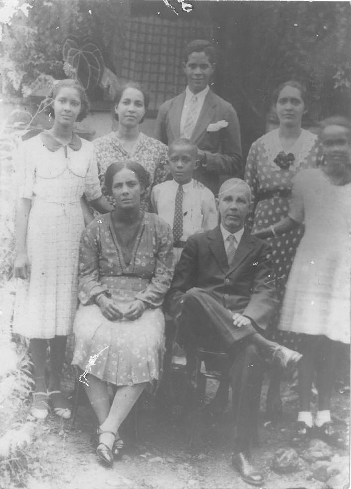 Black and white photo taken outdoors under a tree, with a garden wall and vegetation behind. John stands at the centre, surrounded by his siblings, with parents sitting at the front of the group.