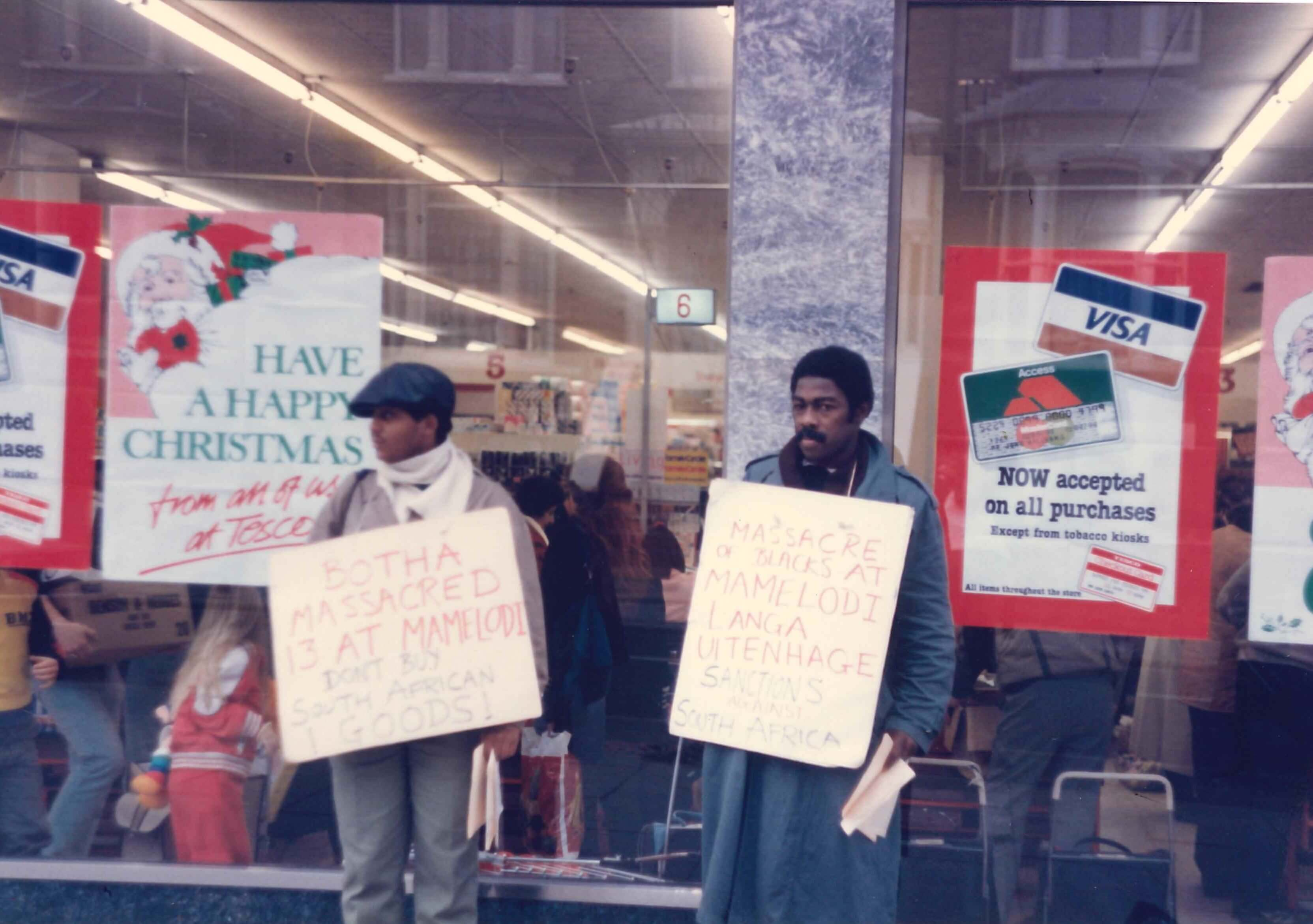 Colour photo shows Michael La Rose and Roxy Harris standing in front of the supermarket windows. A Christmas poster in the window helps to date the picture. Both protestors are wearing neck boards denouncing the Mamelodi massacre in South Africa a month earlier and encouraging shoppers not to buy South African goods.