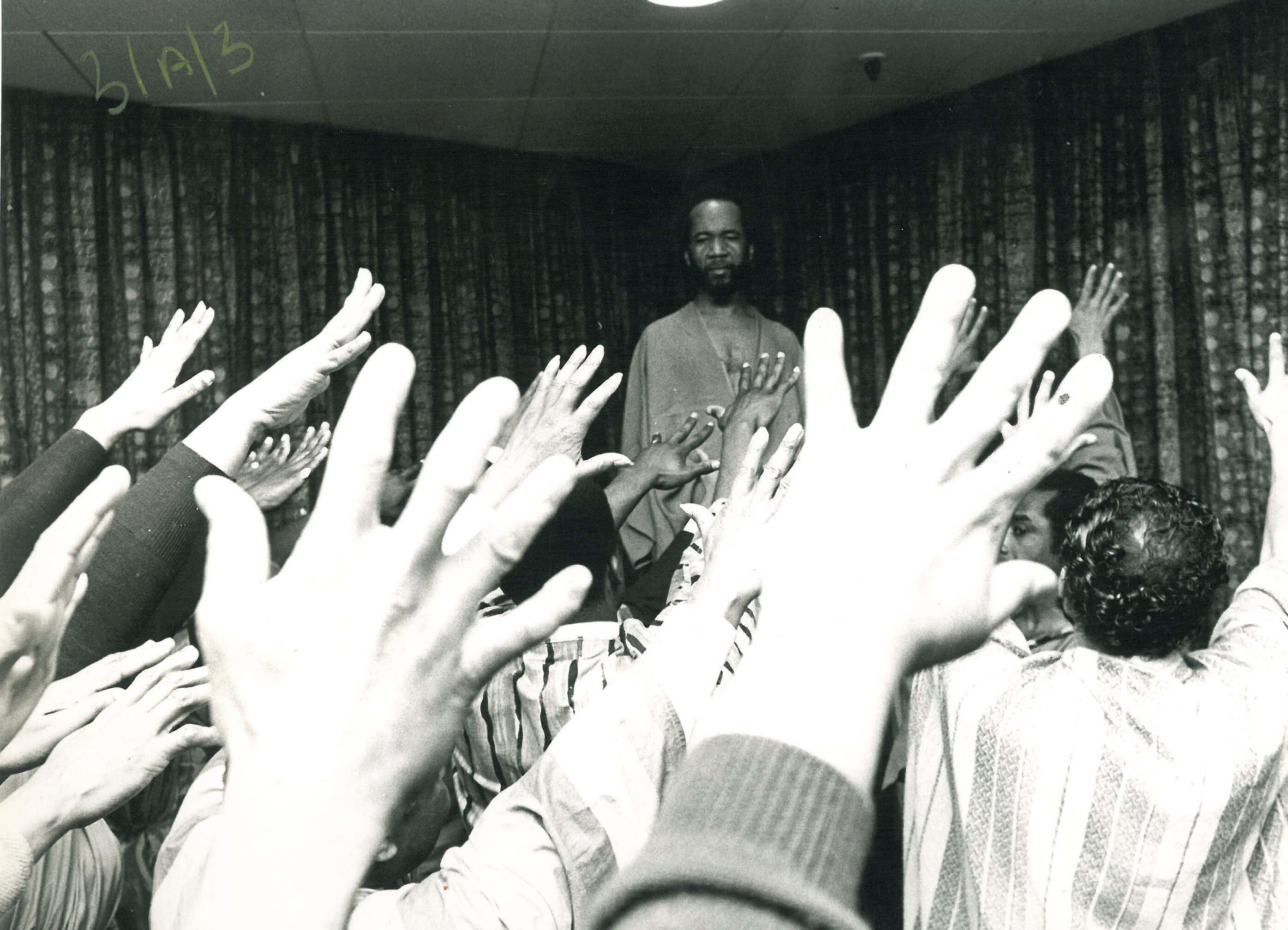 A sea of hands raised towards George Browne, playing Jesus, as he stands on stage before the kneeling crowd.