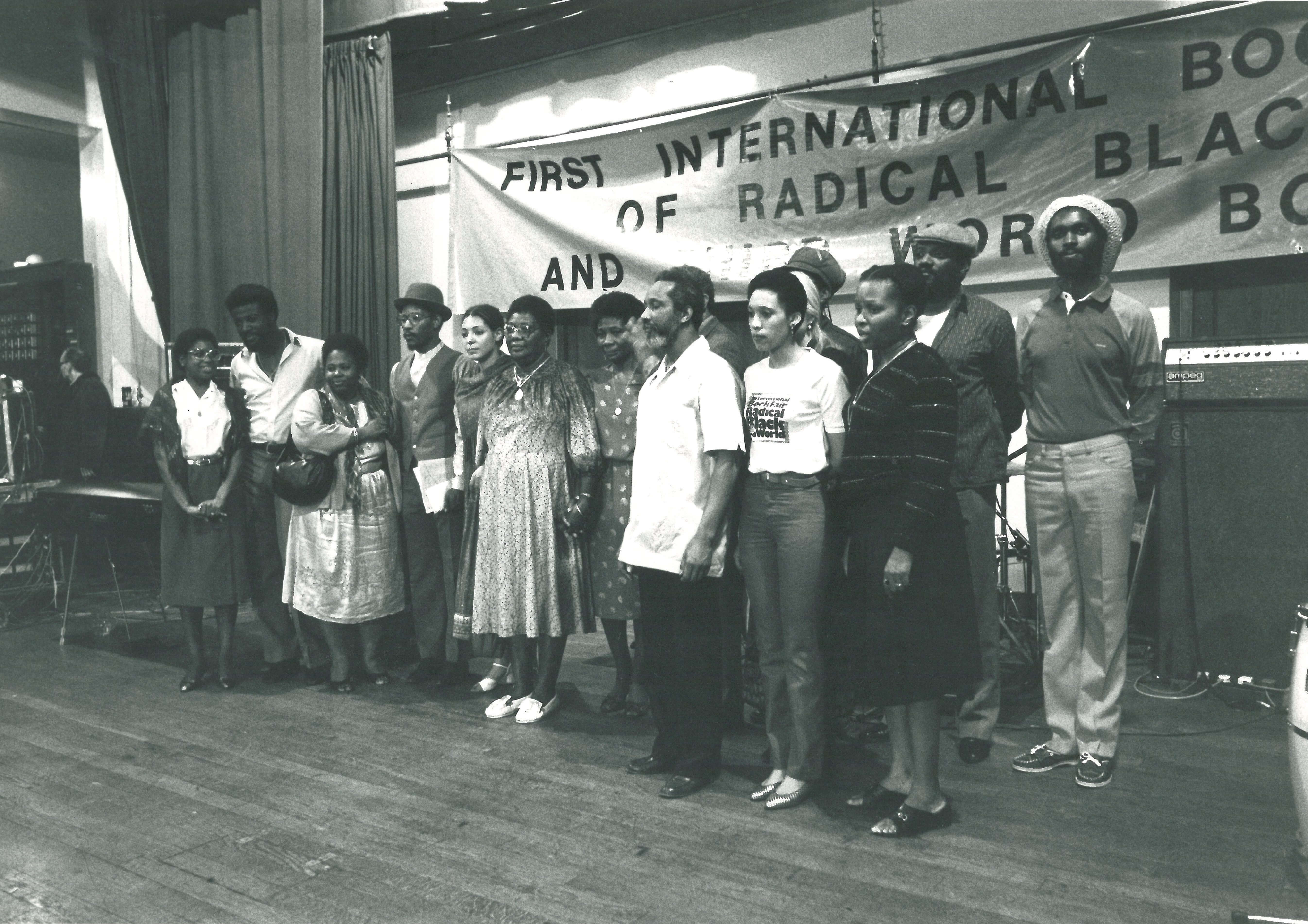 15 individuals are standing on stage, as if posing for a group photo. A banner hangs behind, indicating that this is the first international book fair to be held. The group includes Linton Kwesi Johnson, Eric and Jessica Huntley, Darcus Howe and Janice Durham.