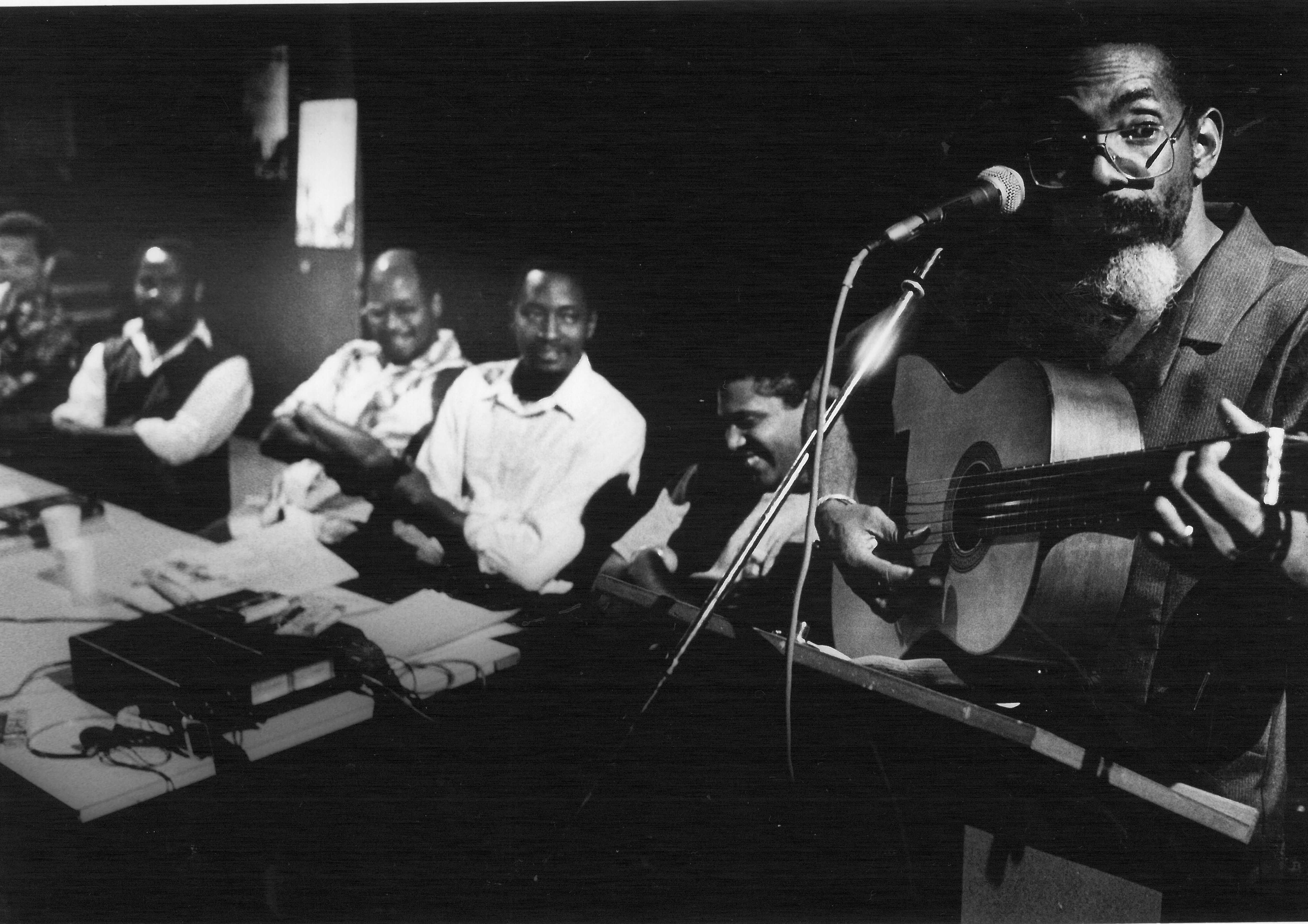 Chalkdust is seen in close-up on the right of the picture, singing and playing a guitar. To the left, 5 individuals can be seen seated at a table, including Michael La Rose, Felix Edinborough, Teddy Belgrave and Gus John.