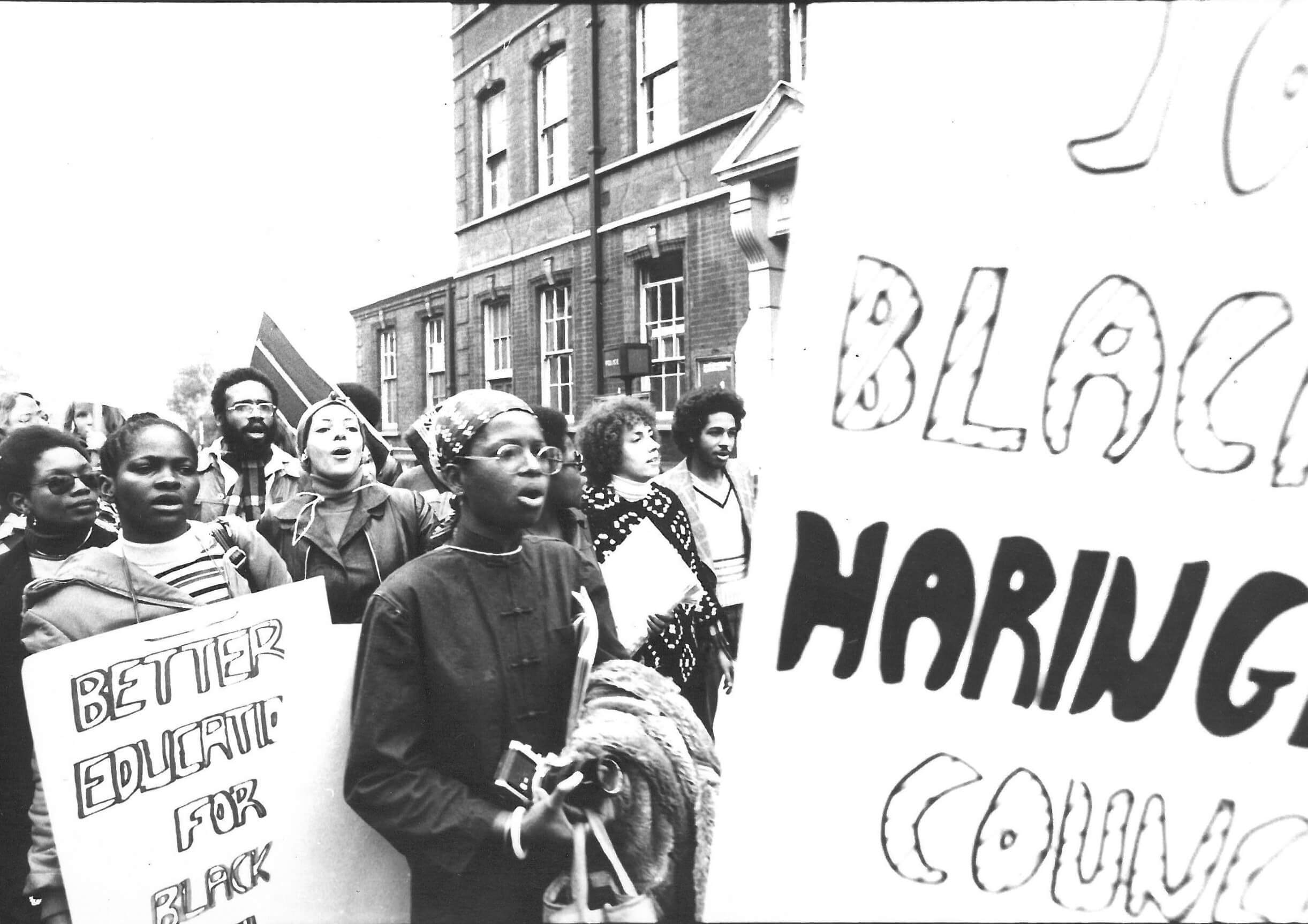 Black and white photo showing protestors with neck boards and placards calling for a better education for black children. The placard nearest the camera cannot be seen in full, but the slogan is protesting against Haringey Council.