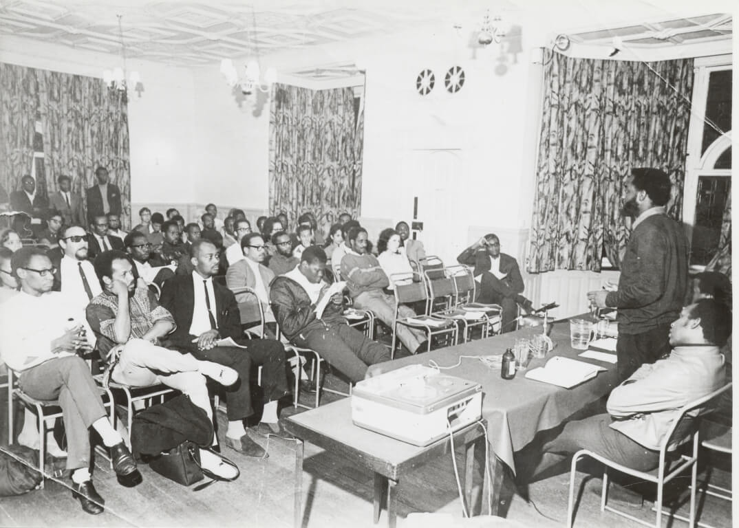 Black and white photo taken inside the West Indian Students Centre, focusing on the audience. Three individuals are shown in a panel discussion on the right of the picture, with one person standing to address the audience.