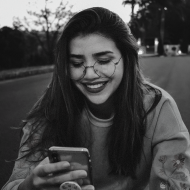Young adult woman with glasses and long hair smiling at her iPhone