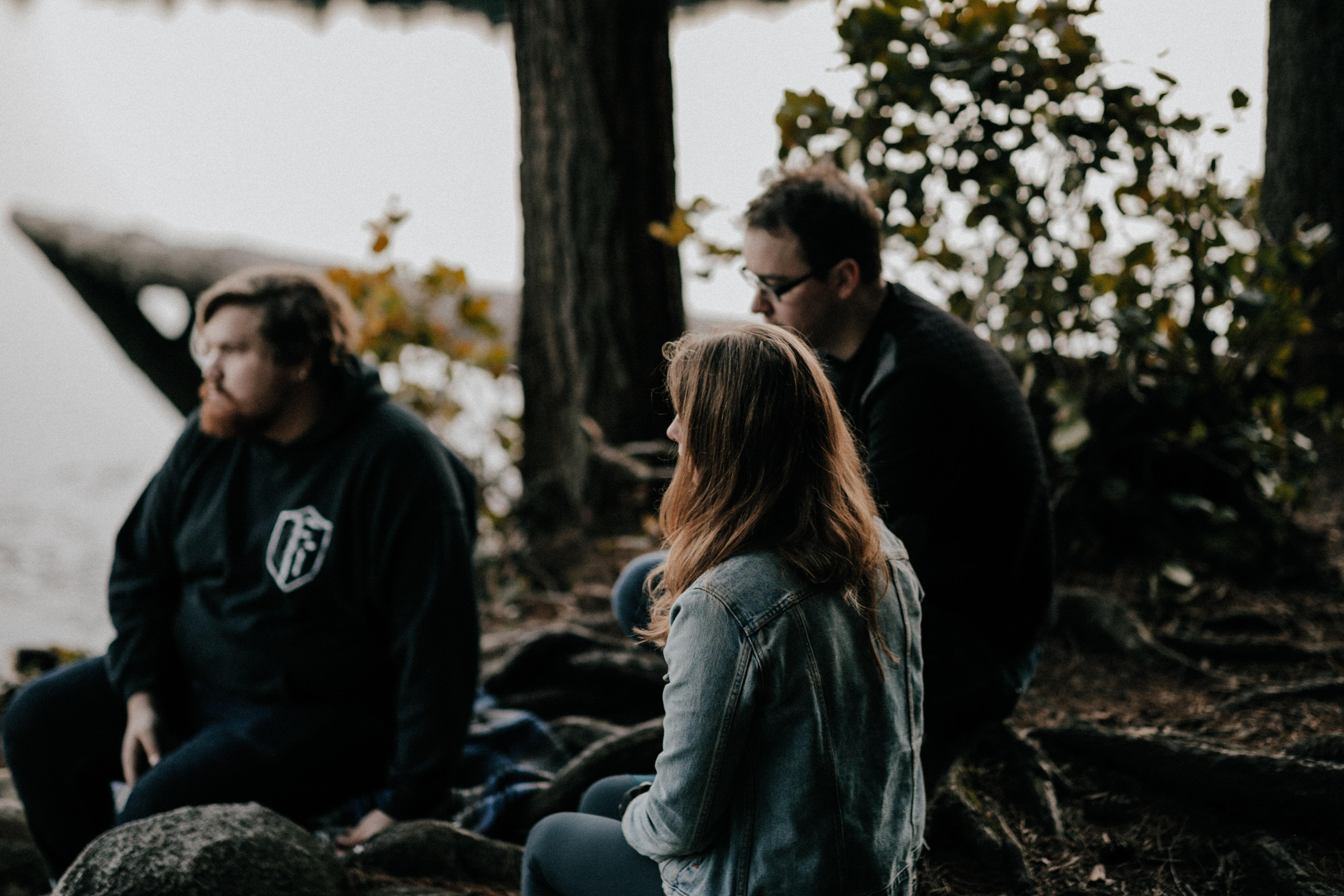 3 people sitting outside talking