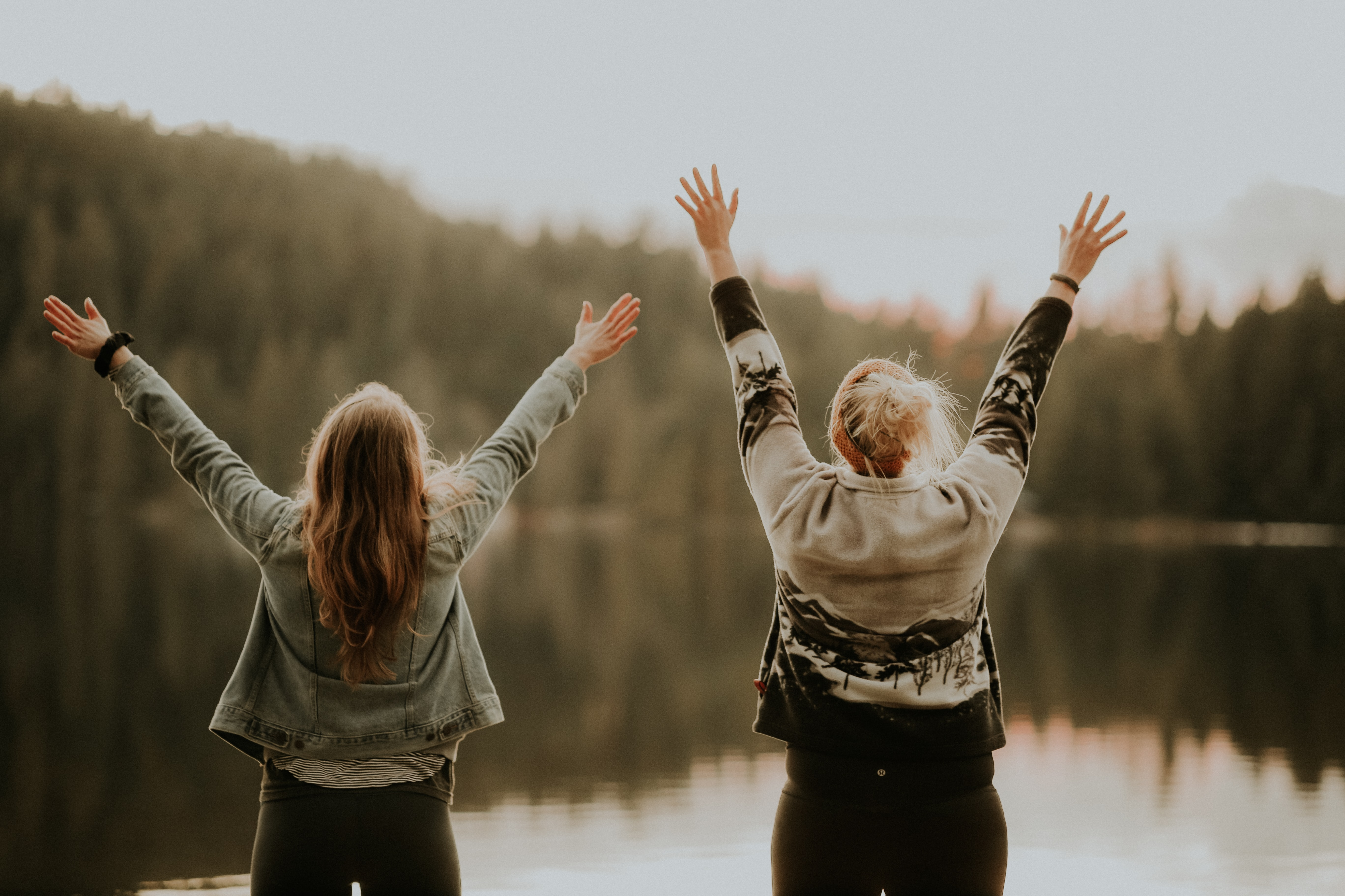 Two woman standing with arms raised in front of a lake
