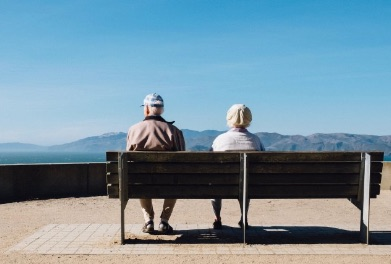 Two Elderly people enjoying a day in the sun on a Bench