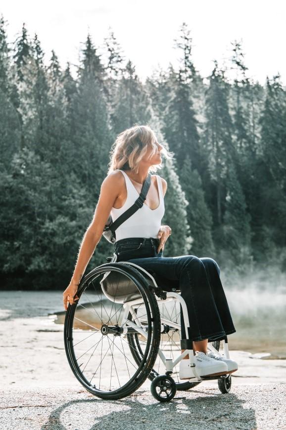Descripción de la imagen: Hay una mujer joven en silla de ruedas manual, lleva puesto unos vaqueros, una camiseta de tirantes, unas deportivas y un bolso. Está disfrutando de un espacio natural. Al fondo se ve mucha vegetación y un río.