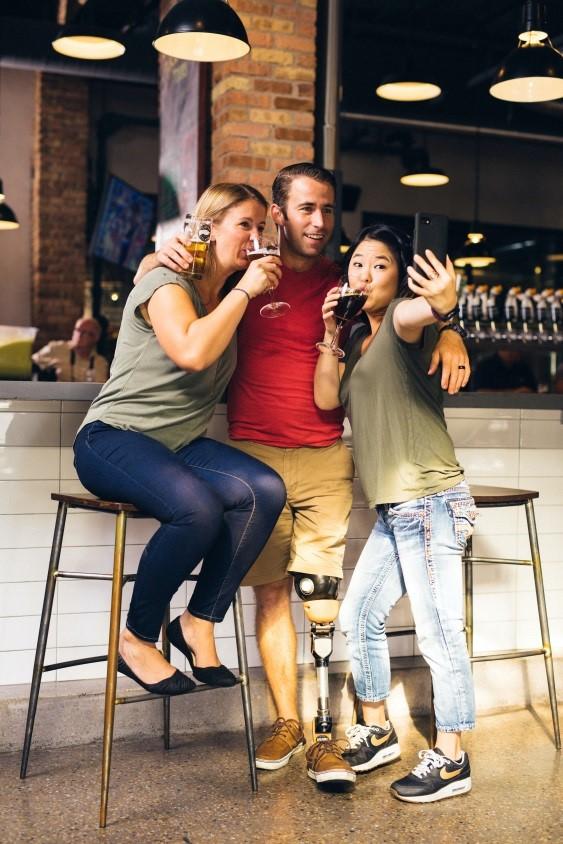 Hay un grupo de amigos, dos chicas y un chico, en un bar. Las chicas llevan puesto vaqueros, camiseta y calzado cómodo. Una de ella está sentada.                            El chico tiene una prótesis de pierna, lleva pantalones cortos, camiseta  y deportivas.                Los tres están bebiendo cerveza y están mirando al móvil porque se están haciendo una foto. Están contentos, disfrutando del momento.