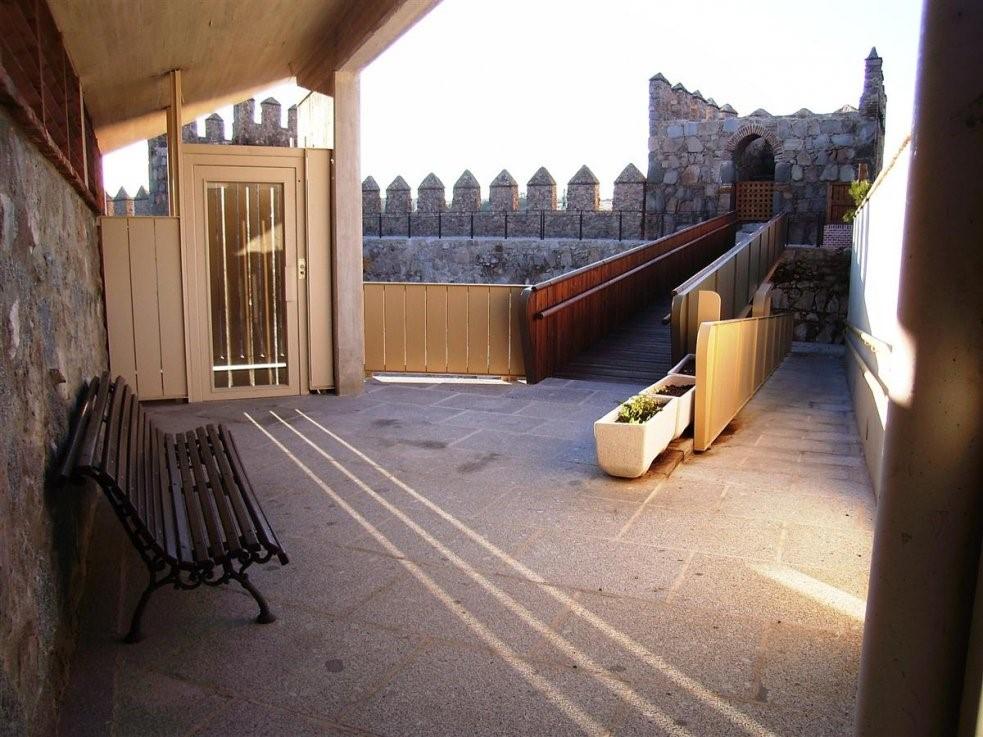 Una parte de la muralla de Ávila. A la izquierda, hay un banco de madera y un ascensor. El suelo es completamente llano y accesible. A la derecha, encontramos la muralla que está unida con la anterior zona gracias a una pasarela completamente accesible.