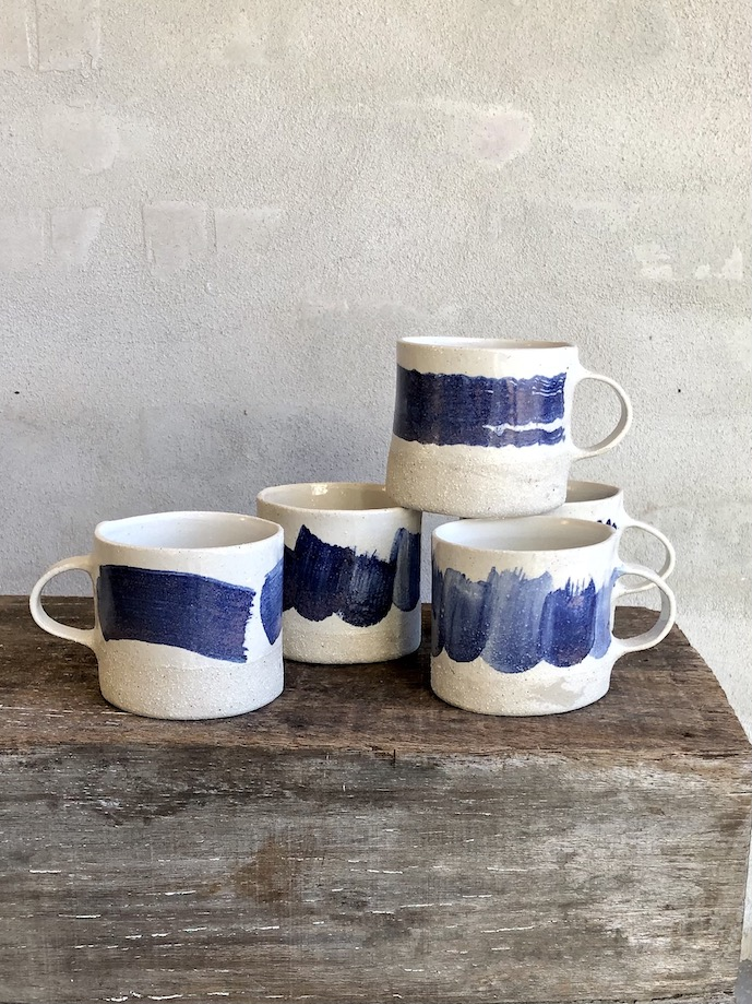 Håndbyggede kop med blå striber.