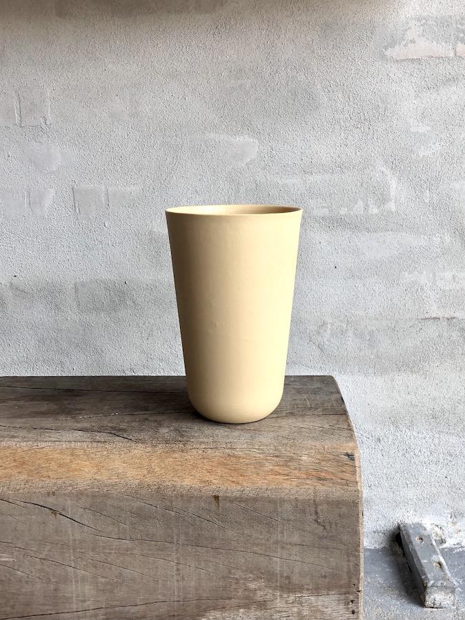 Håndstøbt vase i porcelæn. Høj. Okkergul.