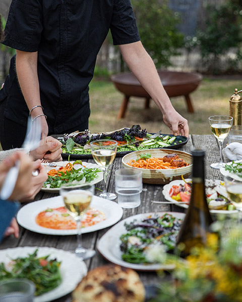 photo of chef placing the plate on a dining table outside