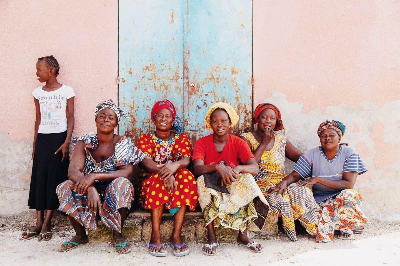Cinq femmes assises et une petites filles sourient