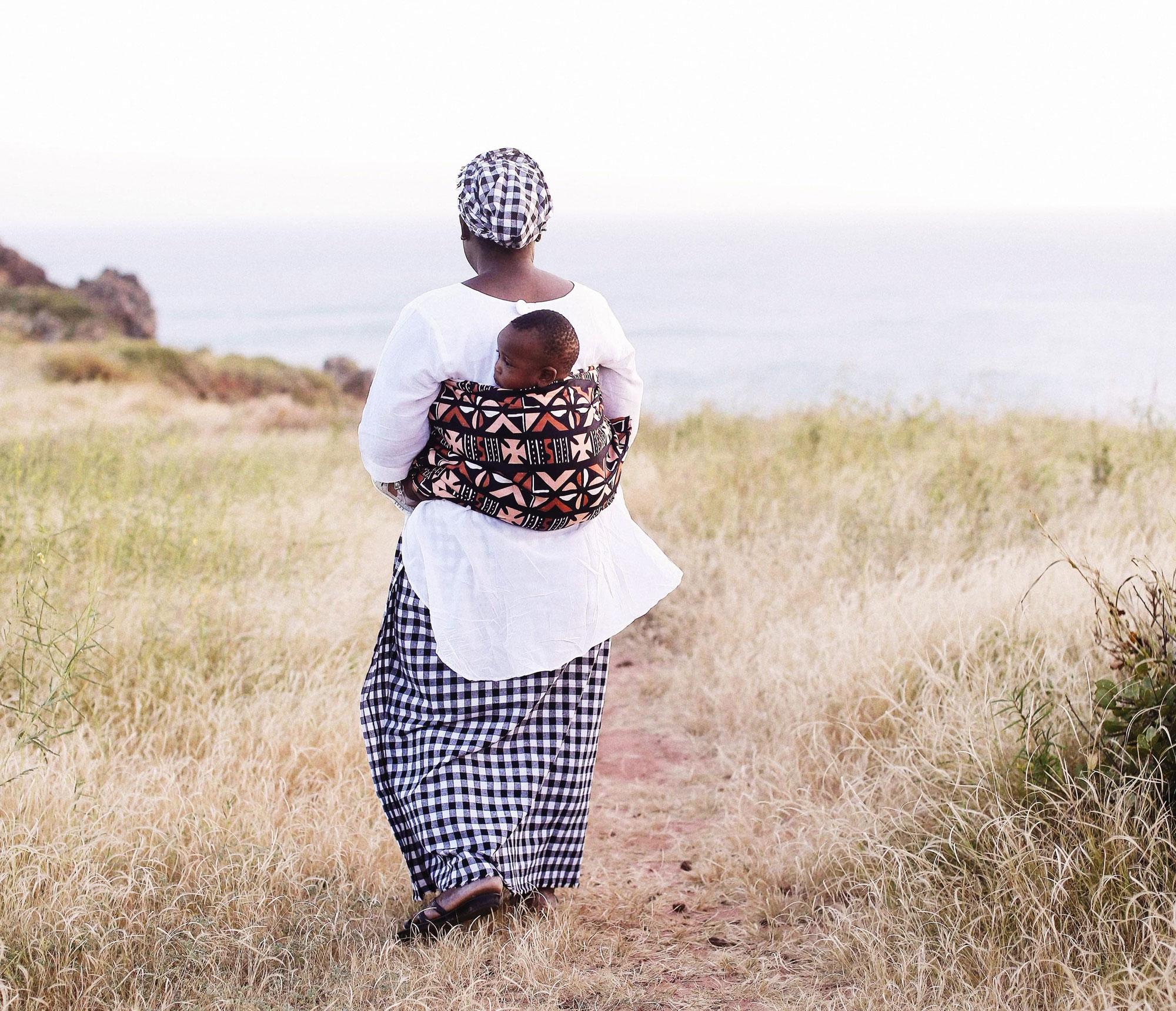 Femme portant son enfant dans un mbotou le long de la mer