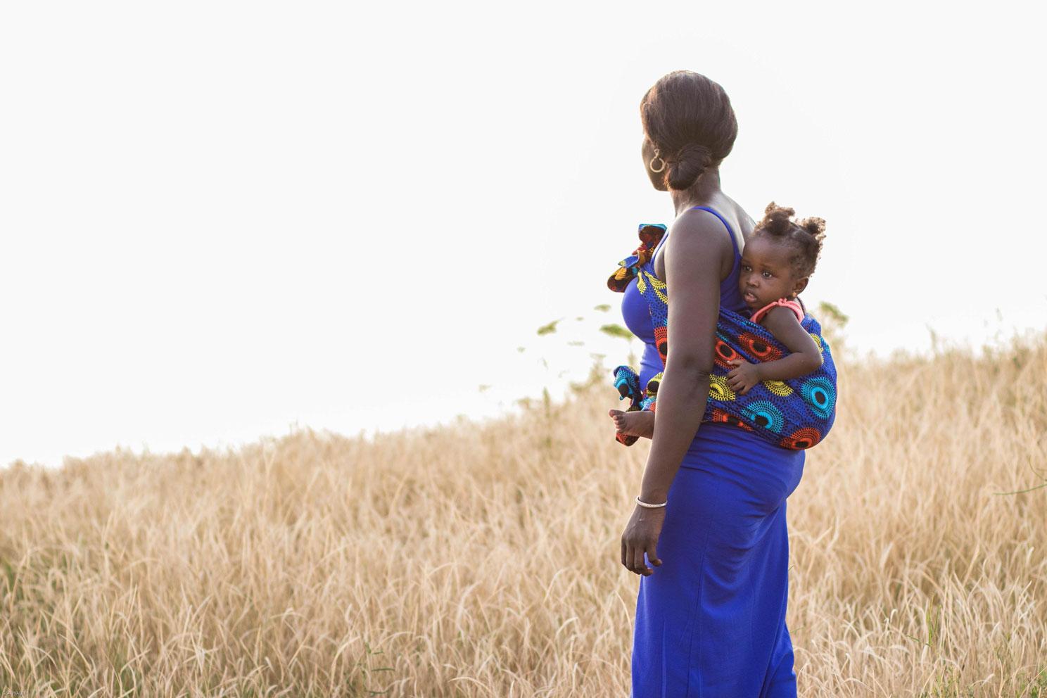 Une femme dans les hautes herbes porte son enfant en mbotou