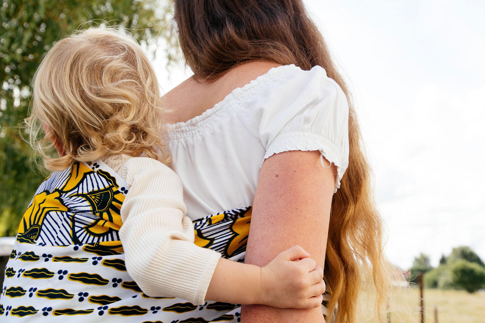 Une femme porte son enfant blond dans un mbotou blanc et jaune
