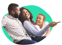 A family watching TV. There is a dad and a mom and their daughter. The mom is point a remote at the TV and they're all smiling and laughing. Clearly, these people have really enjoyed their experience with saving money with BillFixers and are now enjoying more free time.