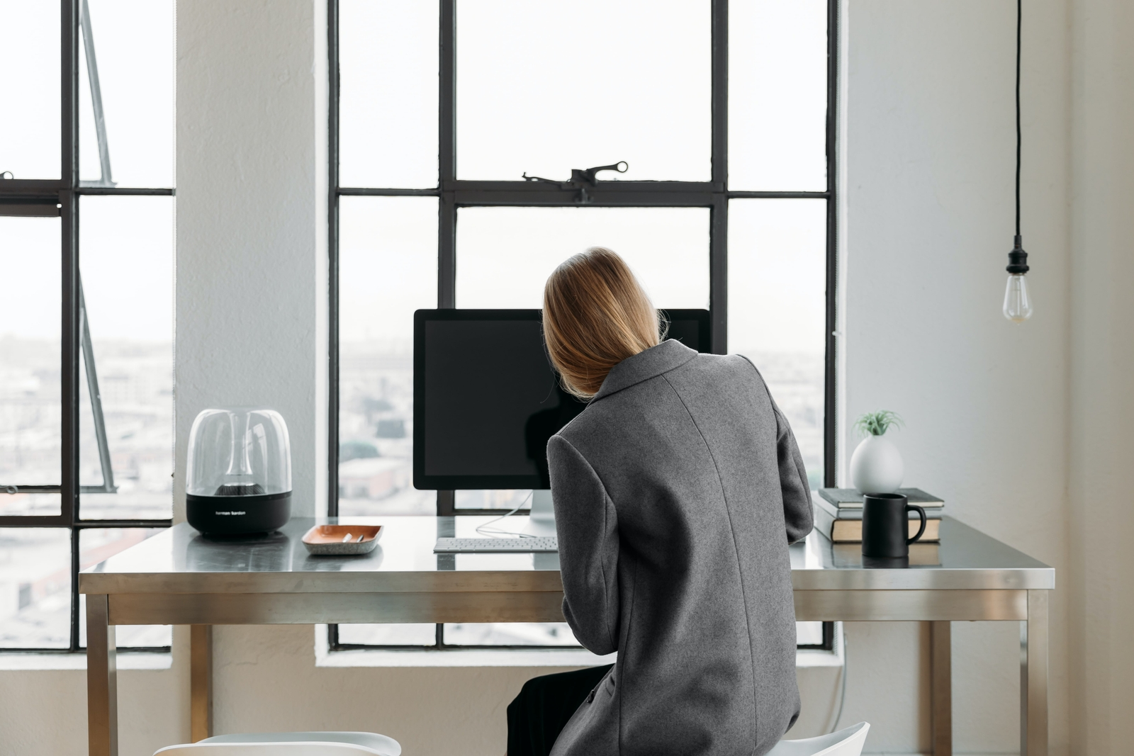 A women in front of her desk writing things down on a computer.