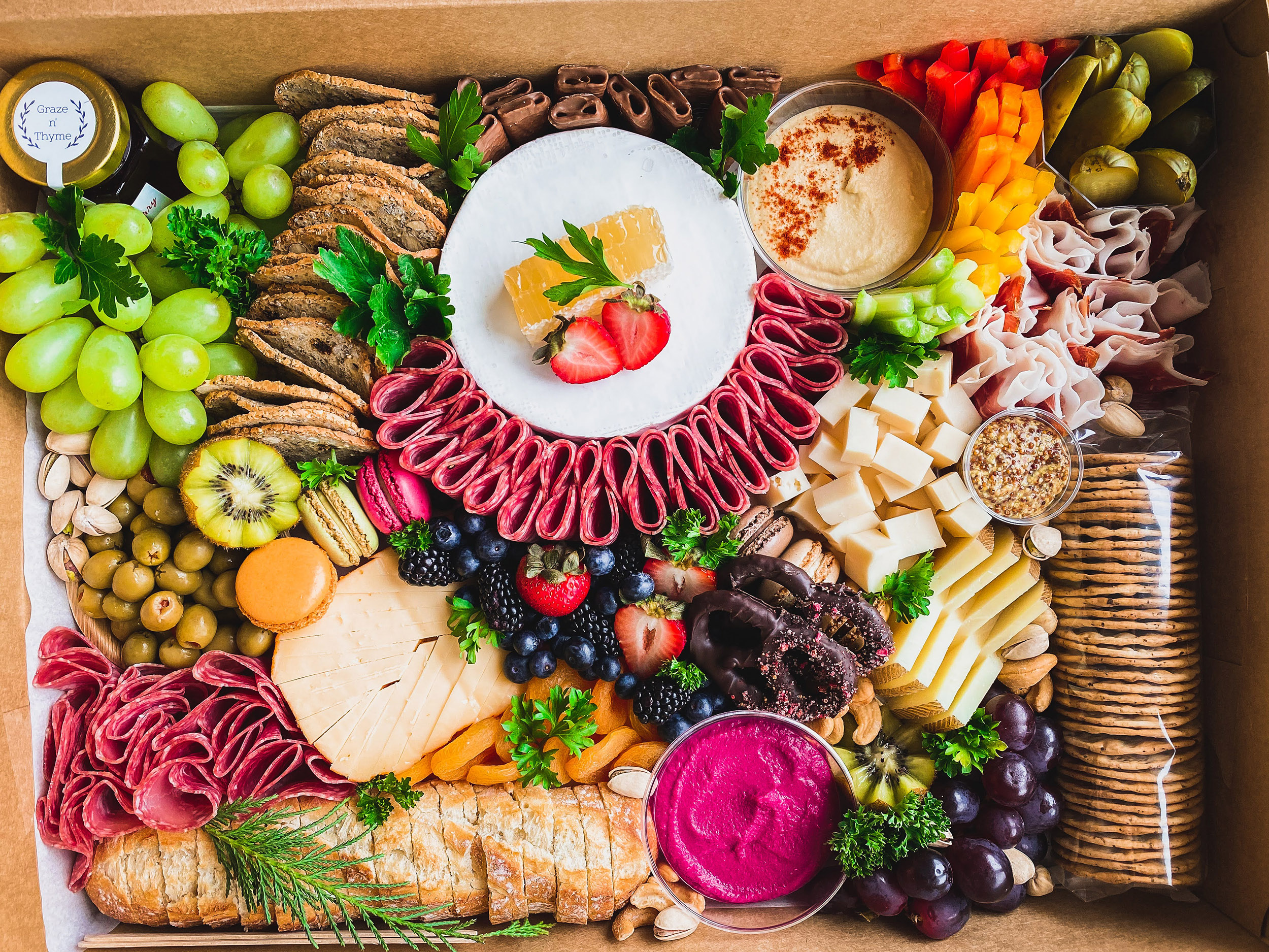 Graze box filled with delicious meats, cheese, fruits, veggies, nuts, bread, honey, and handmade dips