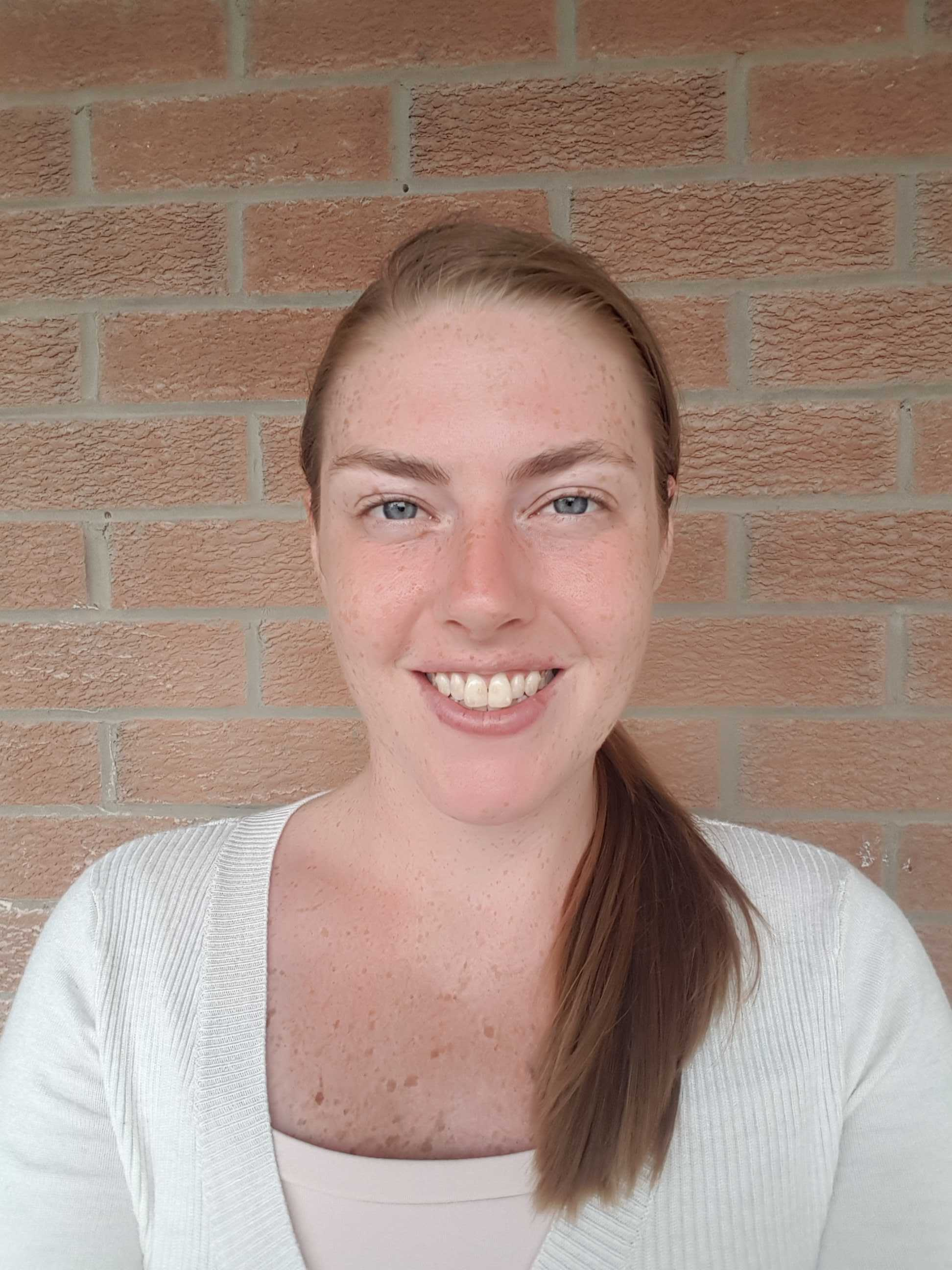 Profile Image of Nicolle White, hair tied in a low ponytail, smiling with the red brick background. Female, red hair, freckles, white shirt.