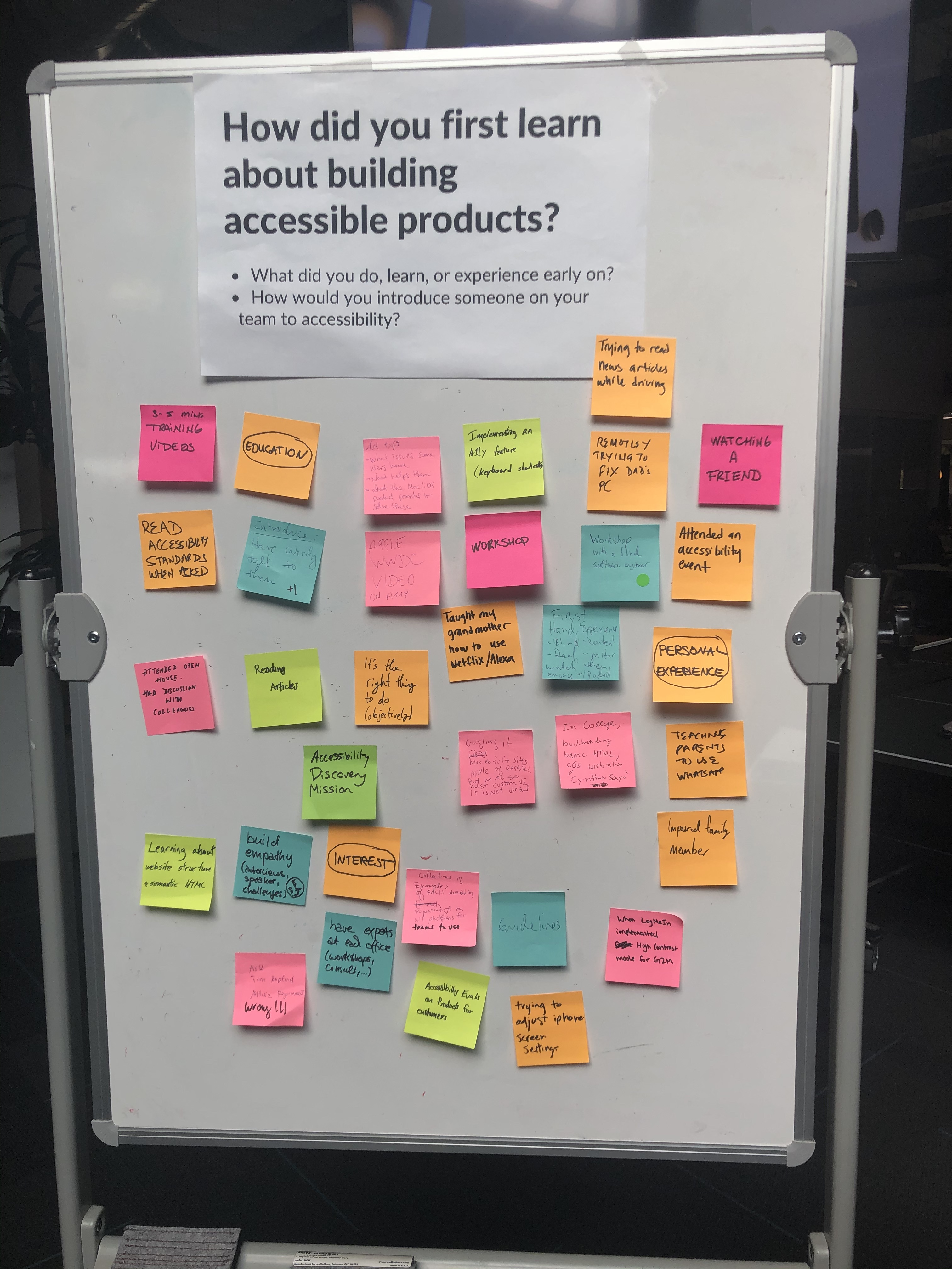 "A whiteboard with a question on it ""How id you first learn about building accessibility products?"" Below the question are postit notes with individual responses."