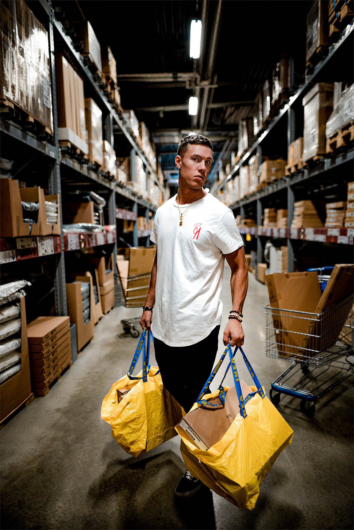 Handsome man in IKEA holding bags wearing shirt by 91 APPAREL