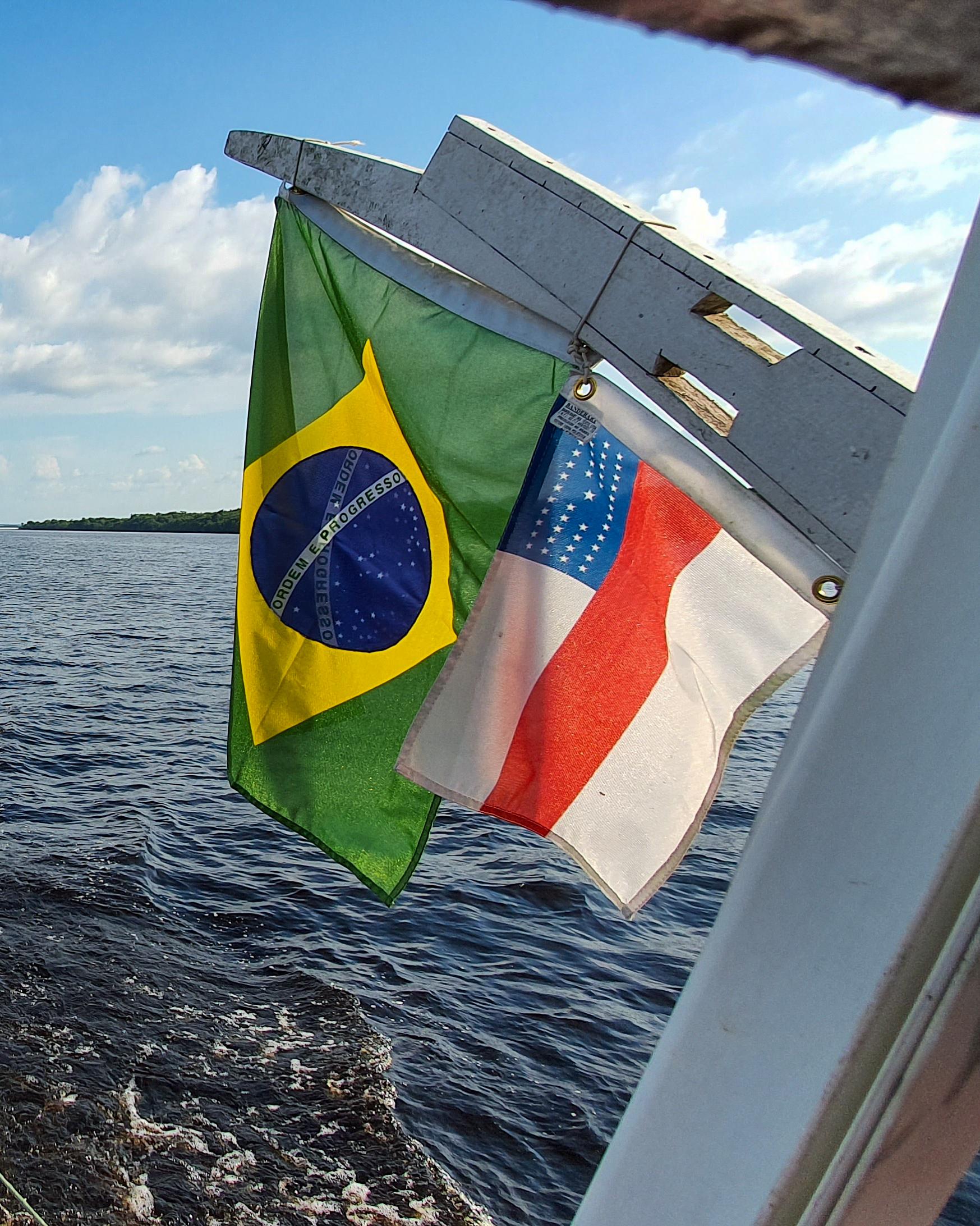 Brazilian flag on a boat on Rio Negro River in Amazon rainforest Brazil