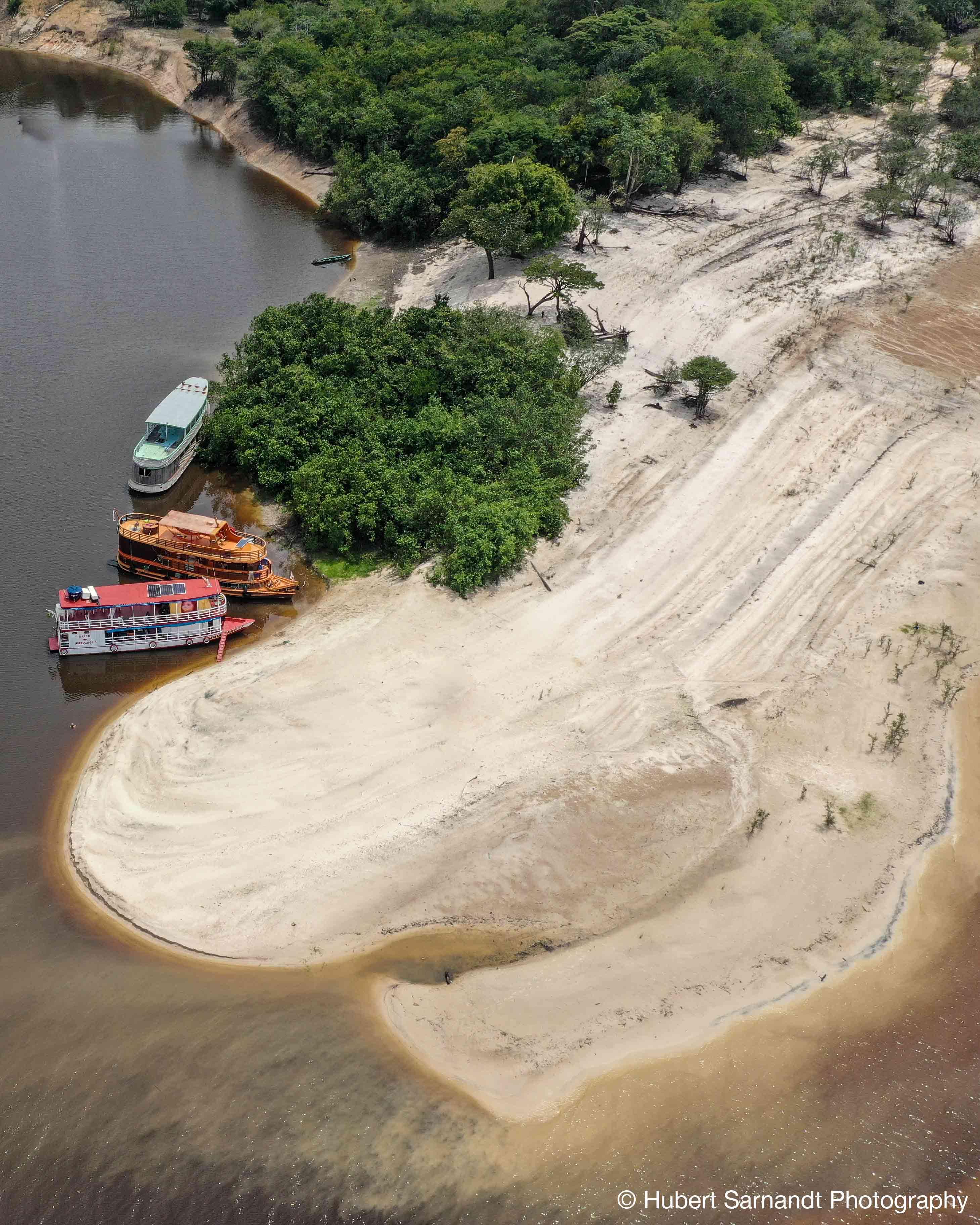 View over three boats in the river Rio Negro in Amazon Rainforest Brazil.