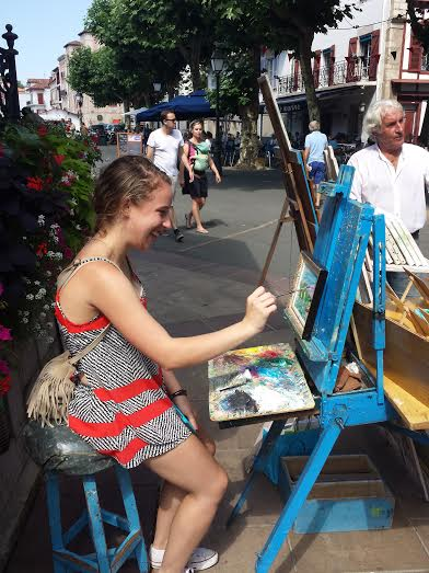 Horizons Abroad French immersion student painting with a street artist in Biarritz, France.