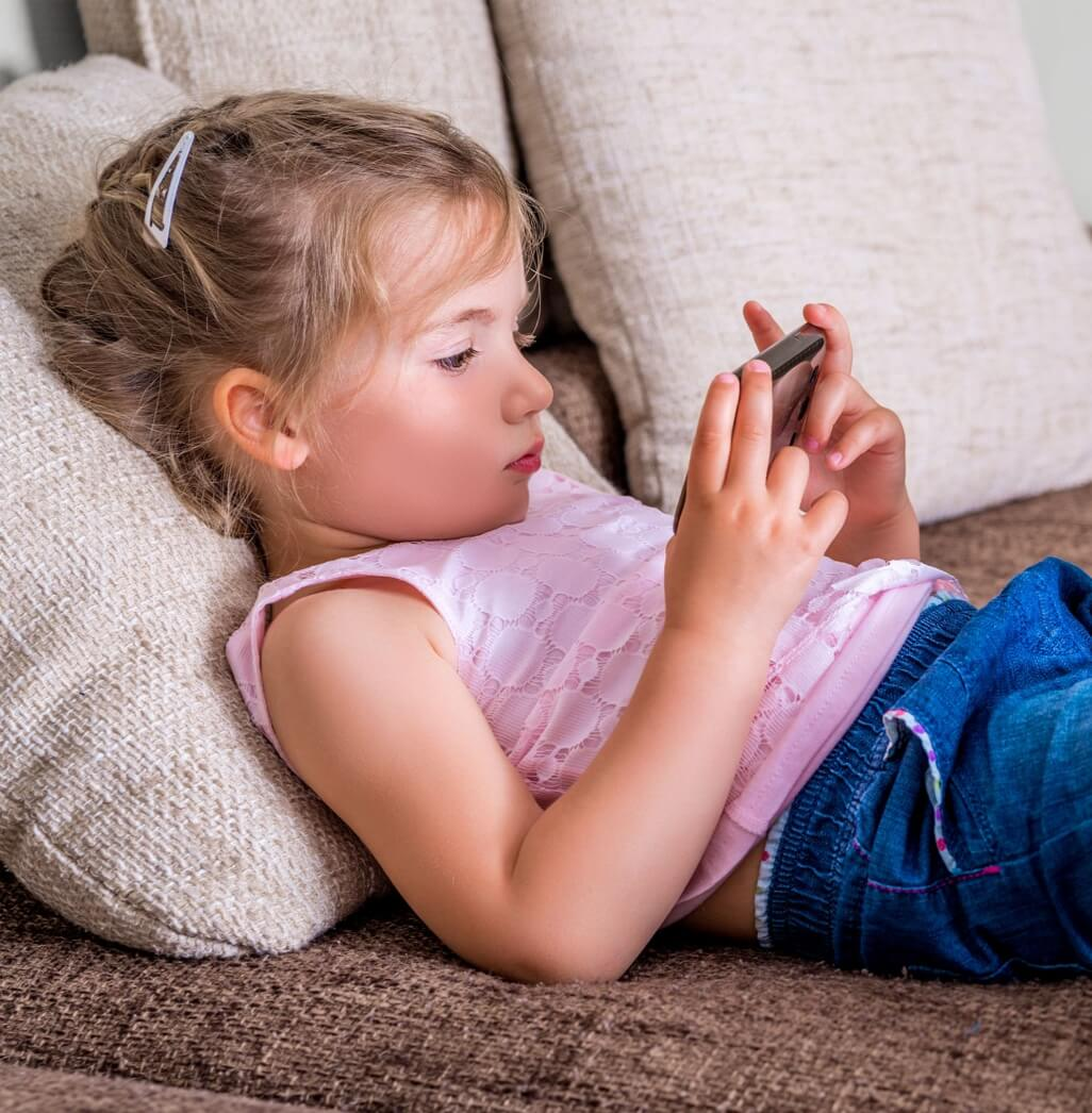 5-year old girl staring at a smartphone screen.