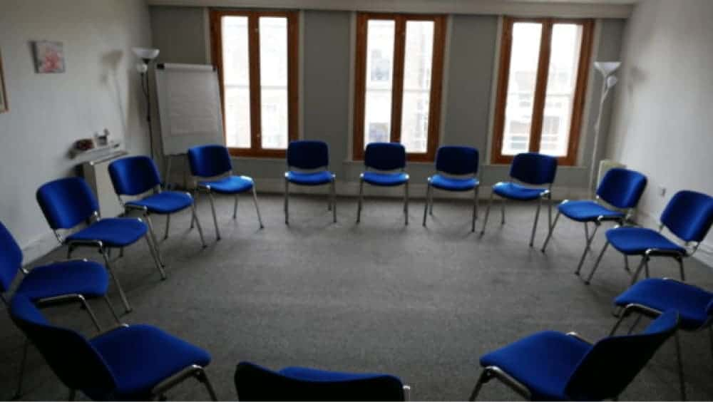 Bright training room with three tall windows and several blue chairs in a circle