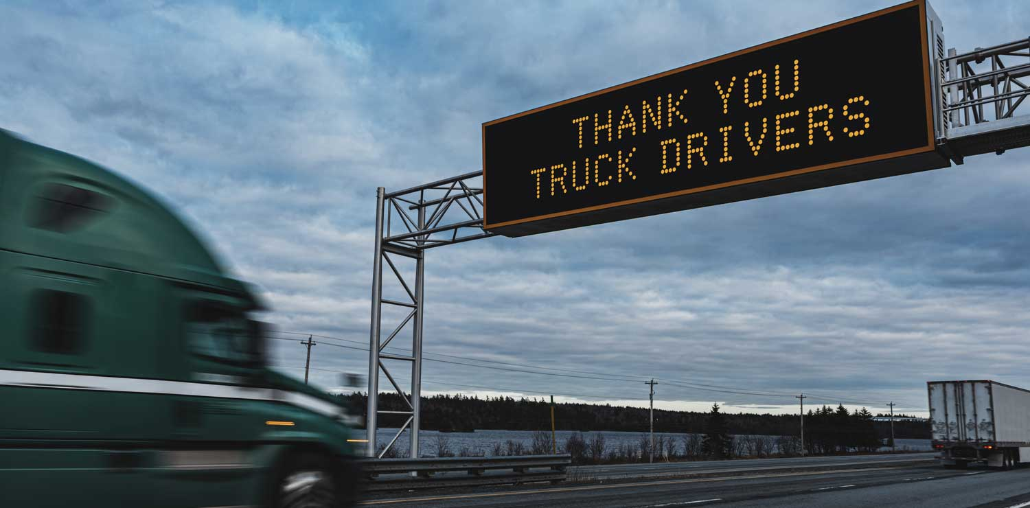 A semi truck approaches a sign that reads thank you truck drivers