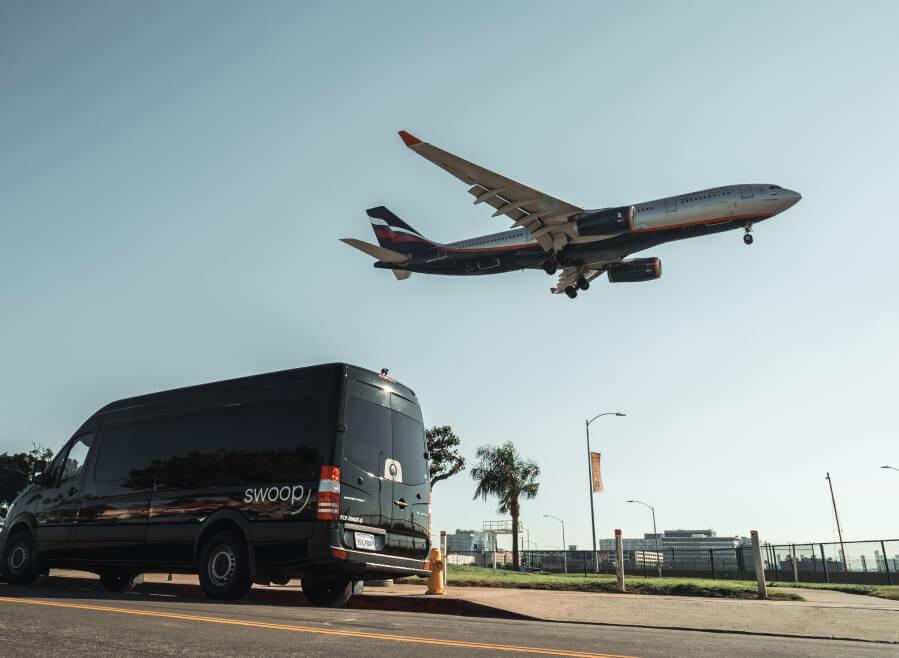 Swoop van with plane landing in the background