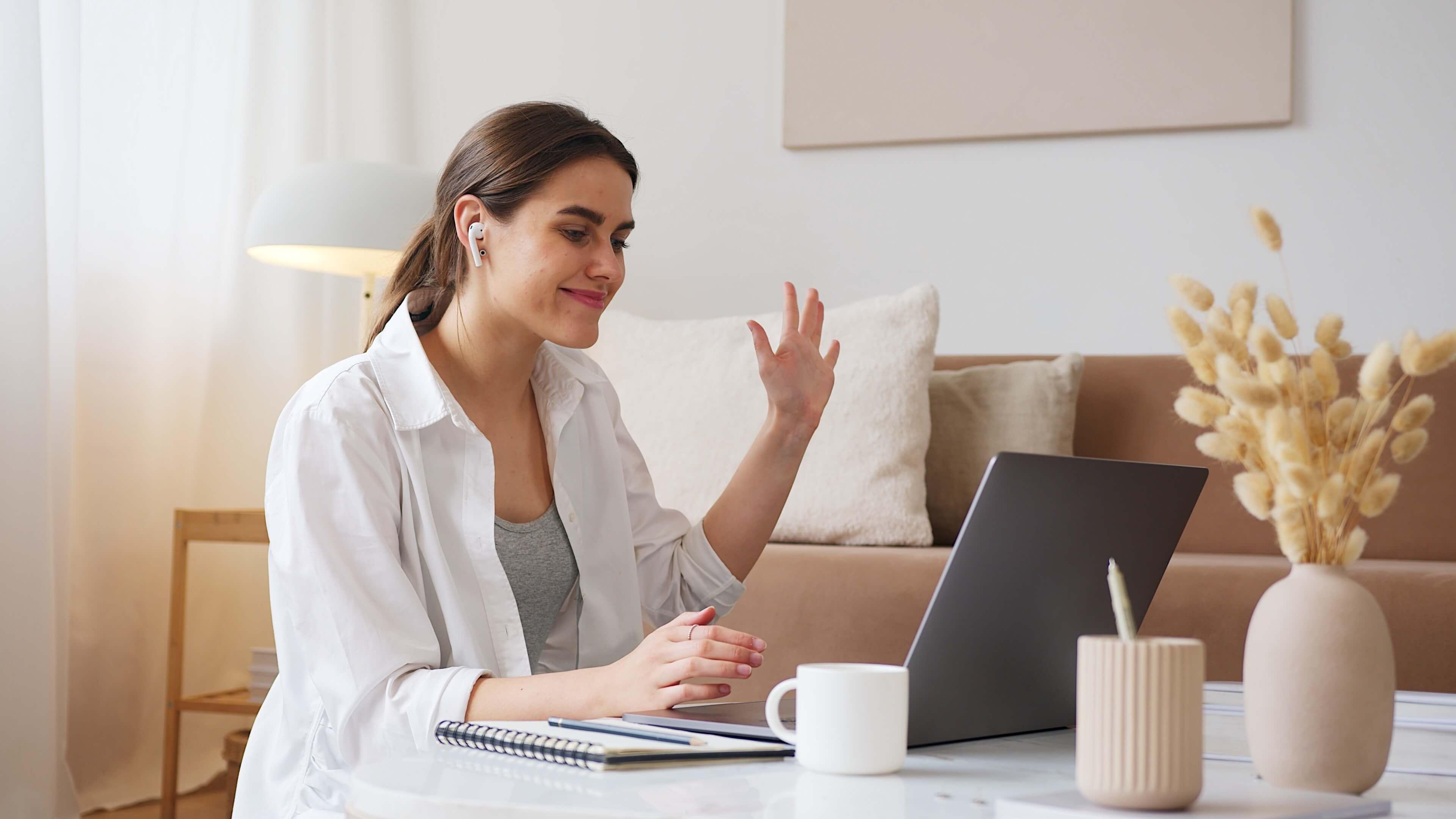 girl waving at the laptop webcam